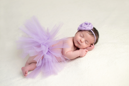 Sleeping, newborn baby girl wearing a lavender colored, crocheted, flower headband and light purple, tulle tutu. Stock Photo