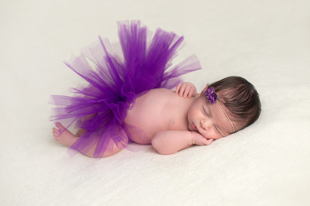 Sleeping, newborn baby girl wearing a purple, tulle tutu and flower headband.