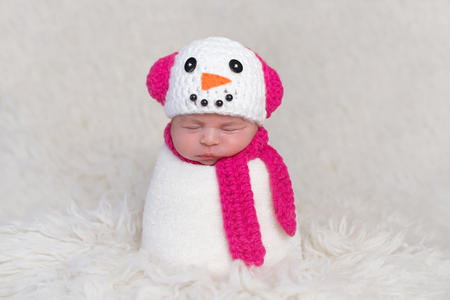 A newborn baby girl wearing a crocheted, bright pink and white snowgirl cap with matching neck scarf. Photographed on a white, flokati rug.