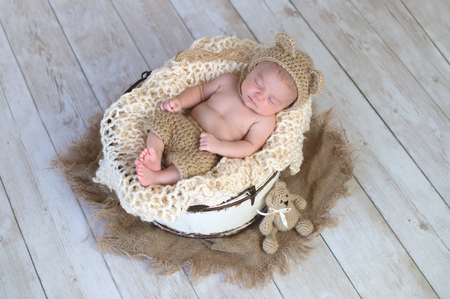 Six week old baby boy wearing a beige, crocheted, bear bonnet and shorts. Imagens