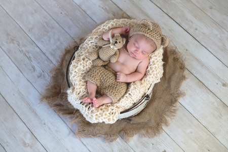 Six week old baby boy wearing a beige, crocheted, bear bonnet. He is sleeping with a matching Teddy Bear. Shot in the studio on a light wood background.