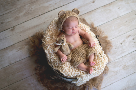 Six week old baby boy wearing a beige, crocheted, bear bonnet and holding a matching Teddy Bear. Shot in the studio on a light wood background.
