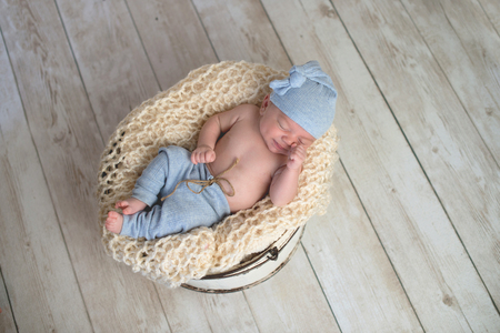 Six week old baby boy wearing light blue pjs and lying in a round, bucket. Imagens