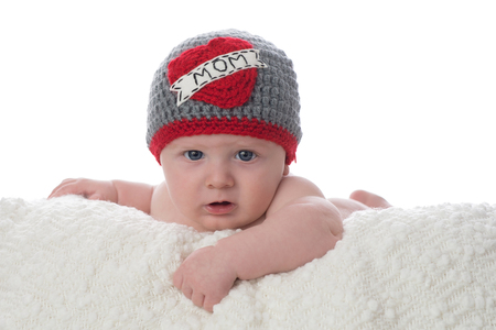 A 2 month old baby boy lying on his stomach on a white blanket. He is wearing a crocheted hat that says, Mom on it. Shot in the studio on a white background.