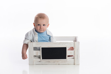 A seven month old baby boy sitting in a white chalkboard crate. Shot in the studio on a white, seamless backdrop.