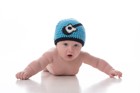 A 2 month old baby boy lying on his stomach on a white, seamless background. He is wearing a crocheted hat that has a guitar graphic on it. Shot in the studio on a white background.