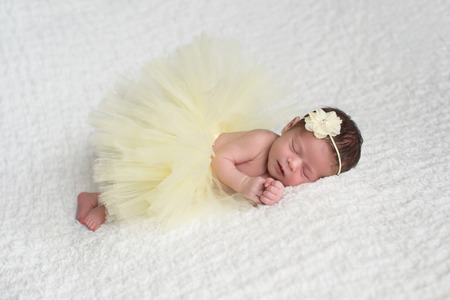 Sleeping, newborn baby girl wearing a yellow flower headband and tutu.