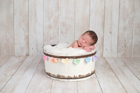 A two week old newborn baby girl sleeping in a little, wooden bucket with a rainbow colored heart garland. Shot in the studio on a white, wooden background.