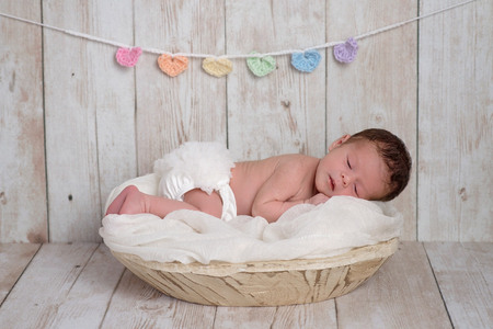 A two week old newborn baby girl sleeping in a wooden bowl. There is a pastel colored, heart shaped garland on the white, wooden background.