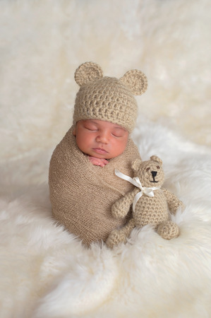 Nine day old newborn baby boy wearing a tan, crocheted bear hat. He is sleeping upright while swaddled with a stretch wrap.