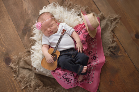 A nine day old, sleeing baby girl wearing jeans and holding a tiny acoustic guitar. She is lying in a wooden crate lined with sheepskin and a pink bandana.