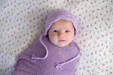 One month old baby girl  wearing a bonnet and swaddled in a lavender purple wrap.