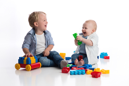 A two year old boy playing with his seven month old baby brother playing with building blocks. Shot in the studio on a white, seamless backdrop.