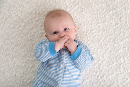 A 2 month old baby boy lying on his back on a white blanket. He is wearing blue and white striped pajamas and has his hand in his mouth and is looking at the camera.