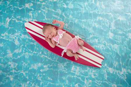 Two week old newborn baby girl lying on a tiny, pink and white surfboard. She is wearing a pink, crocheted bikini.