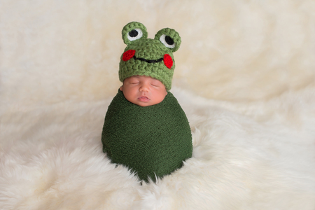 Nine day old newborn baby boy wearing a green frog hat. He is sleeping upright while swaddled in a stretch wrap. Imagens