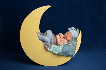 Studio portrait of a ten day old newborn baby boy wearing pajama bottoms and a sleeping cap. He is sleeping on a moon shaped posing prop.