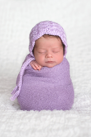 A two week old newborn baby girl wearing a lavender, crocheted bonnet. She is sleeping upright while swaddled in a light purple stretch wrap.