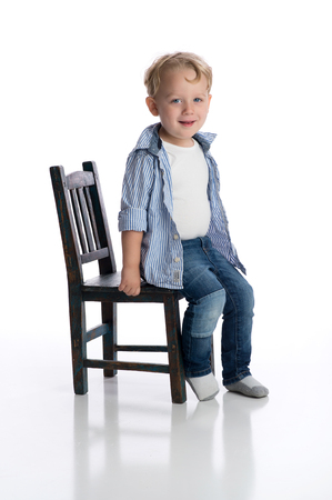 A smiling two year old boy sitting on a childs chair. Shot in the studio on a white, seamless backdrop.