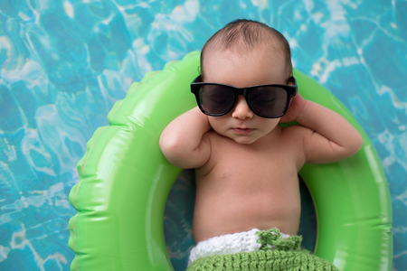 Two week old newborn baby boy sleeping on a tiny, green, inflatable swim ring. He is wearing green, crocheted board shorts and black sunglasses. Imagens