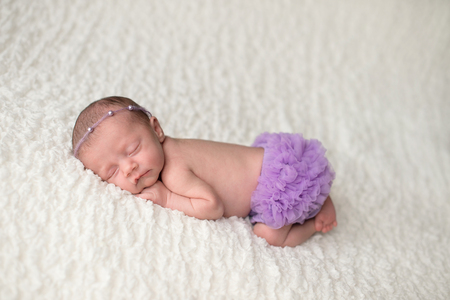 Portrait of a sleeping, 2 week old newborn baby girl wearing frilly, lavender purple bloomers and a pearl headban. Shot in the studio on a white blanket. Imagens