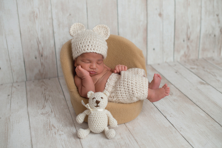 Nine day old newborn baby boy wearing cream colored, crocheted, bear hat and shorts. He is sleeping on a tiny chair with a matching stuffed bear toy next to him.
