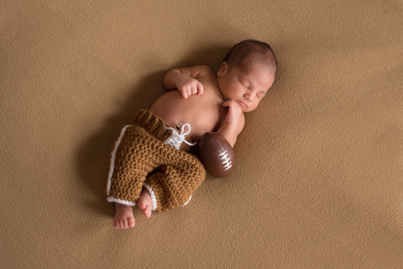 A sleeping, nine day old newborn baby boy wearing crocheted football uniform pants. Imagens