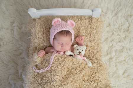 Portrait of a newborn baby girl. She is sleeping in a tiny bed with a stuffed bear and wearing a bonnet with bear ears.