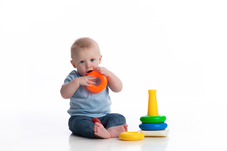 A seven month old baby boy playing with a ring stack toy. Shot in the studio on a white, seamless backdrop.