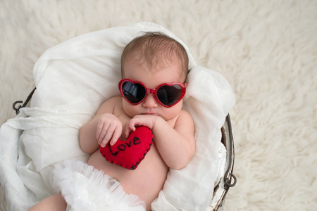 Nine day old, newborn baby girl wearing red, heart shaped sunglasses. She is holding a heart shaped pillow with the word, Love written on it. Imagens
