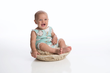 A laughing seven month old baby boy sitting in a rustic, wooden bowl. Shot in the studio on a white, seamless backdrop.