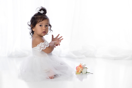 A one year old, baby girl sitting on the floor with a flower. She is wearing a white, tulle dress wtih lace sleeves.