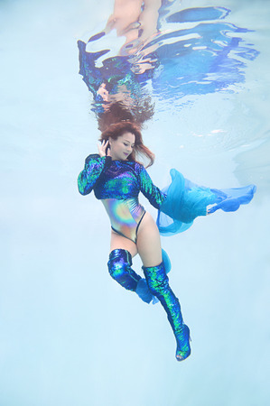 An underwater portrait of a woman wearing green and blue sequined stilletto boots and matching shirt.