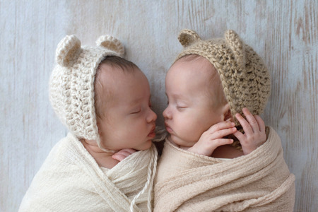 Profile headshot of two, fraternal, twin, baby girls sleeping. They are wearing crocheted bear hats and are swaddled in cream and tan wraps. Imagens