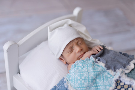 One week old newborn baby boy wearing a white sleeping cap. He is sleeping on a tiny, white bed and covered with a blue, patchwork quilt. Imagens