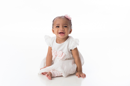A smiling six month old baby girl wearing a white dress. She is sitting on a white, seamless background. Imagens