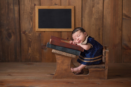 One week old newborn baby girl wearing a dress and sleeping on a stack of vintage books at a tiny school desk. Imagens