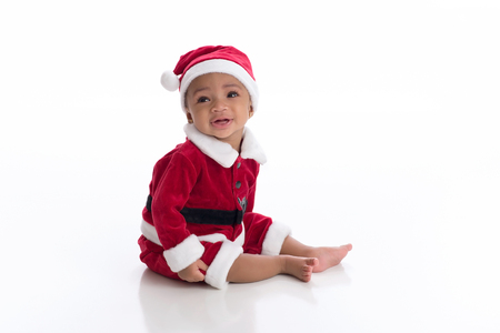 Smiling six month old baby girl wearing a Santa Claus costume. Photographed in the studio on a white, seamless background.