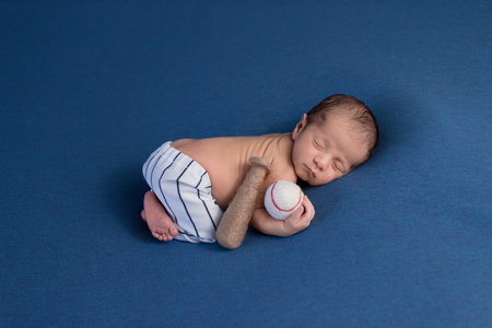 A week old, sleeping, newborn baby boy wearing baseball uniform pants and holding a baseball.