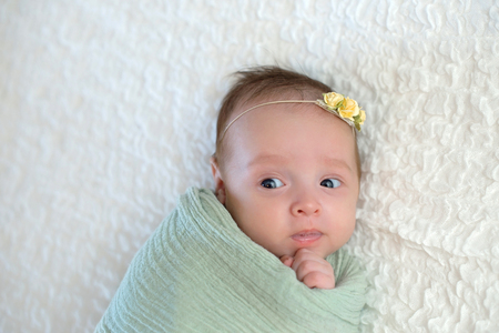 Alert one month old baby girl swaddled in a mint green colored wrap. She has a funny expression on her face. Imagens