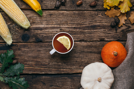 Autumn vegetables:tea, pumpkins and corn with yellow leaves on a wooden background top view