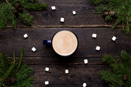 Cocoa with marshmallows on a wooden background with spruce winter theme