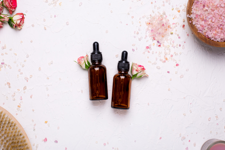 Natural oil bottles with flowers and bath salt on white background