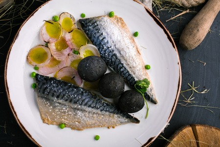 Restaurant dish with mackerel and onions