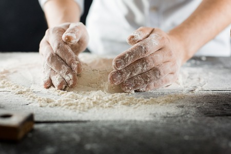 Male chef hands knead the dough with lots of flour on the kitchen table macro view