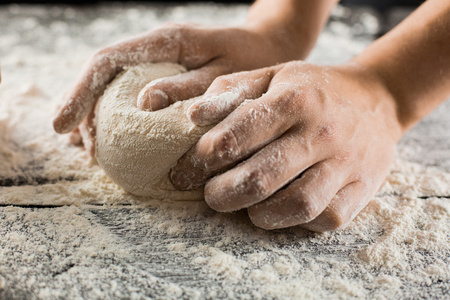 Male chef hands knead dough with flour on kitchen table side view 版權商用圖片