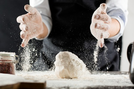 Cook kneads dough with flour on kitchen table stop motion 免版税图像