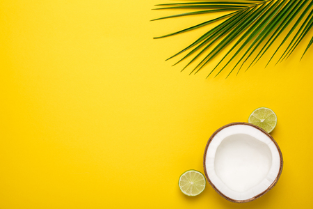 Tropical coconut, palm and lime on a yellow background top view
