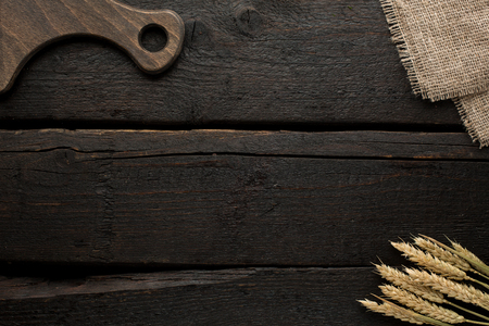 Wooden background with board and wheat top view