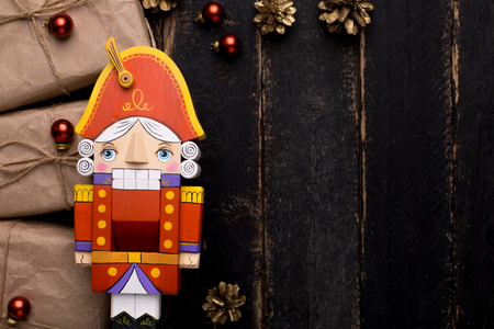 Nutcracker toy with gifts with a New Year's decor on a wooden background top view